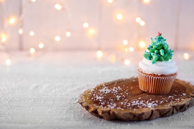 조명이 있는 나무 스탠드에 크리스마스 컵케이크