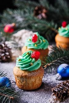 お祝いの雪に覆われた森のクリスマスカップケーキ。新年とクリスマスのお祝いのデザート。