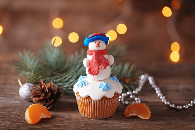 木製のテーブルに装飾が施されたクリスマスカップケーキ