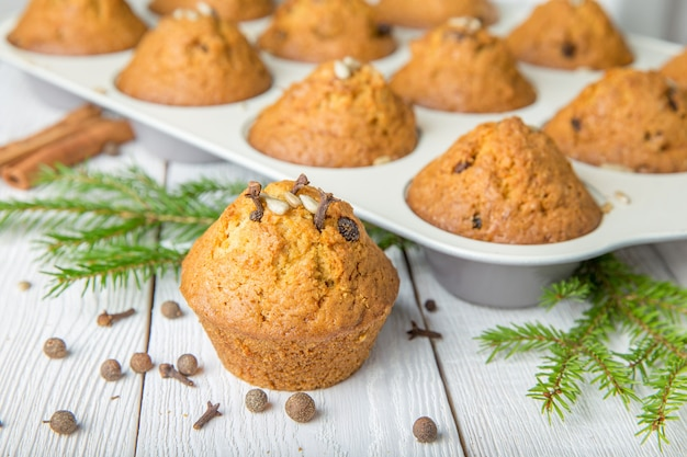 Christmas cupcakes with spices cloves, seeds and nuts in a baking dish on white wooden table
