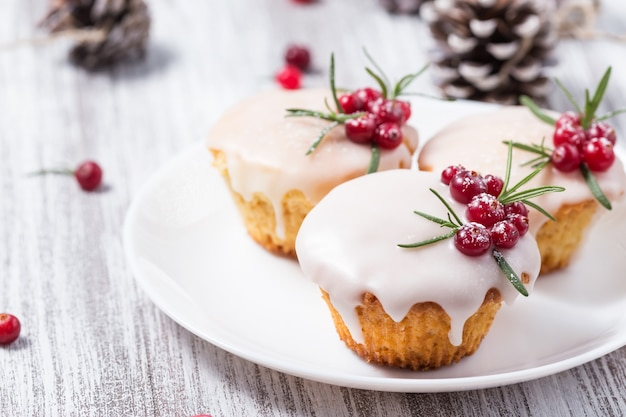 Christmas cupcakes with sugar icing, cranberries and rosemary