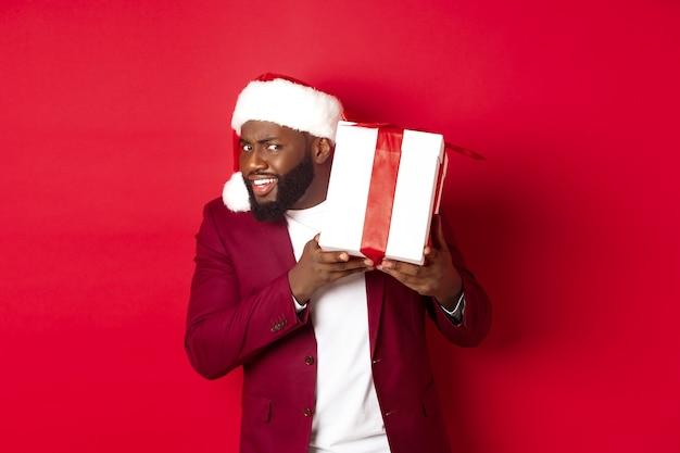 크리스마스. 새해 선물을 흔드는 산타 모자를 쓴 호기심 많은 흑인 남자, 빨간 배경에 서서 상자 안에 무엇이 들어 있는지 궁금하다