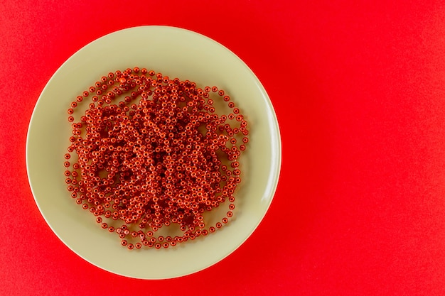 Christmas cutlery and beads. red christmas beads on a green plate. christmas dinner concept. top view