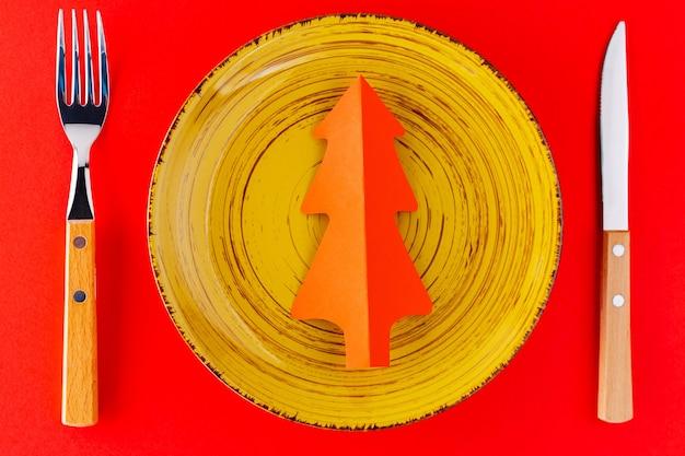 크리스마스 칼. 노란색 접시, 칼 붙이 및 종이 크리스마스 트리와 빨간색 배경에 크리스마스 테이블 설정. 평면도