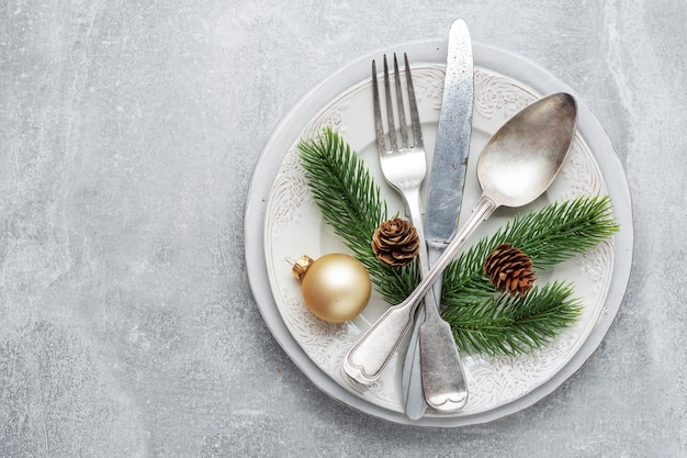 Christmas cutlery on plate with christmas deco on table.