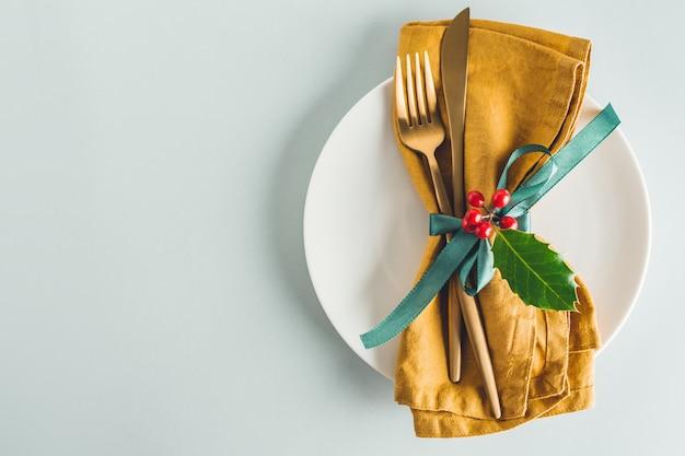 Рождественские столовые приборы с салфеткой на тарелке