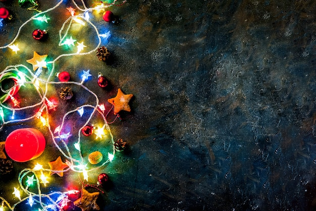 クリスマスガーランド、装飾、ジンジャーブレッド星、キャンドルとクリスマスの暗い背景。トップビューコピースペース