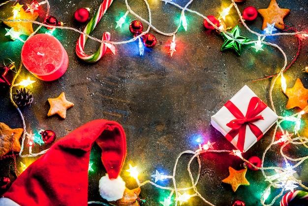 クリスマスガーランド、装飾、ジンジャーブレッド星、ギフトボックス、サンタ帽子、キャンドルとクリスマスの暗い背景。トップビューコピースペースフレーム