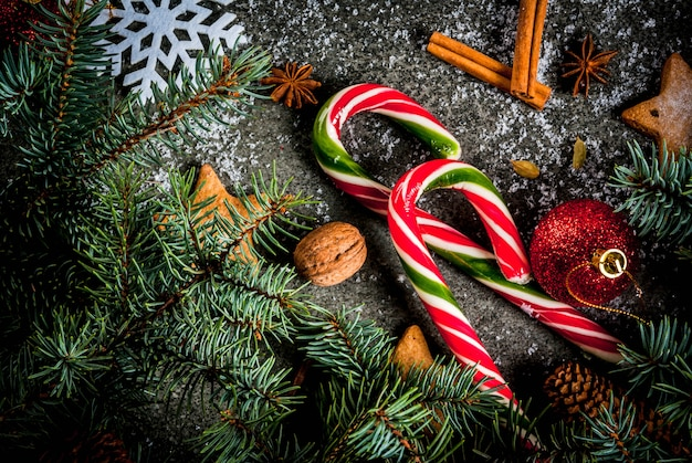 Christmas dark background with christmas tree branches, pine cones, candy cane sweets, gifts, christmas balls