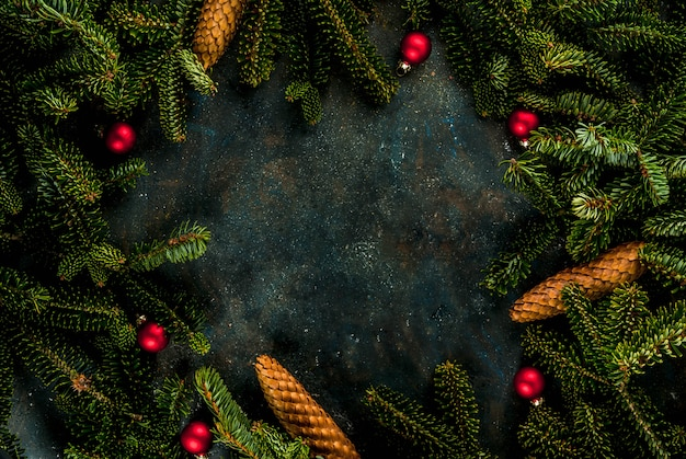 Christmas dark blue background with fir tree branches, pine cones and christmas tree balls copy space above frame