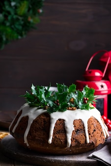 Christmas dark chocolate cake decorated with white icing and holly berry branches with red lattern on a dark wooden