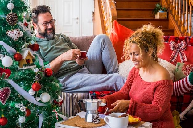 一緒にコーヒーを楽しむ愛の幸せな若い大人のカップルとクリスマスの日の朝の朝食