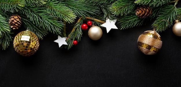 전나무와 어두운 배경에 싸구려 크리스마스 데코. 플랫 레이. 크리스마스 컨셉입니다. 배너.