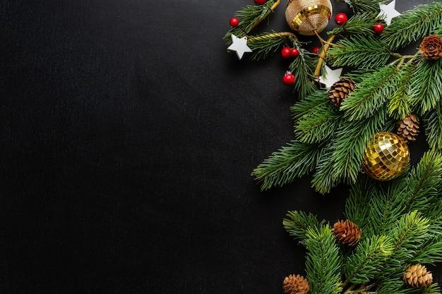 暗い背景にモミとつまらないものとクリスマスデコ。フラットレイ。クリスマスのコンセプト