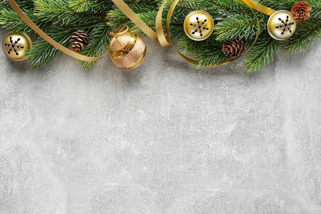 전나무와 회색 콘크리트 배경에 싸구려 크리스마스 데코. 플랫 레이. 크리스마스 컨셉
