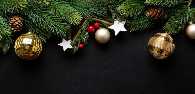 Christmas deco with fir and baubles on dark background. flat lay. christmas concept. banner.