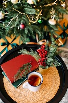 Рождественский декор и чашка чая с гирляндами боке на елке и зеленом бархатном диване