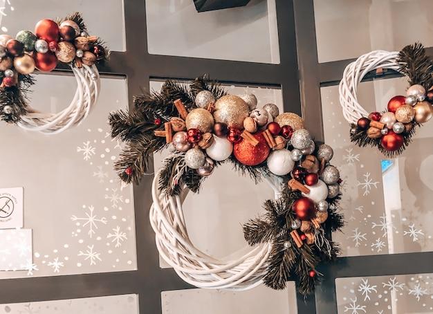 가문비나무 가지가 있는 빨간색과 흰색 공으로 만든 크리스마스 화환 형태로 카페 입구에 있는 크리스마스 장식, 부드러운 흰색 색상의 사진.