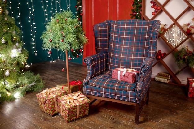 Рождественский декор. яркий интерьер с елкой, большим удобным креслом и яркими гирляндами на стенах. зимние каникулы