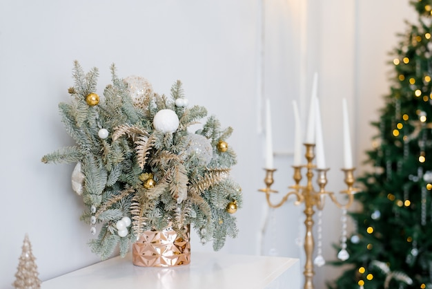 Christmas decor in a classic living room or bedroom in bright colors. spruce branches in gold vases with toys and a gold candlestick on the dresser