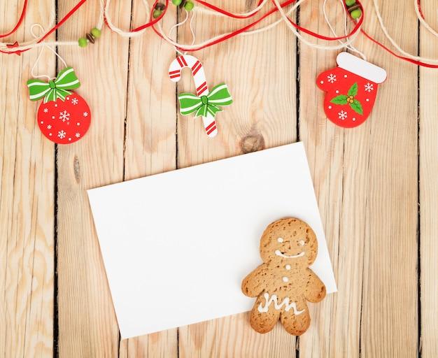 나무 테이블에 복사 공간을 위한 크리스마스 장식, 진저브레드 쿠키 및 카드