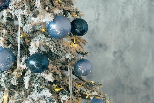 크리스마스 장식. 눈, 빛나는 푸른 유리 공 장신구와 요정 빛 녹색 전나무 나무. .