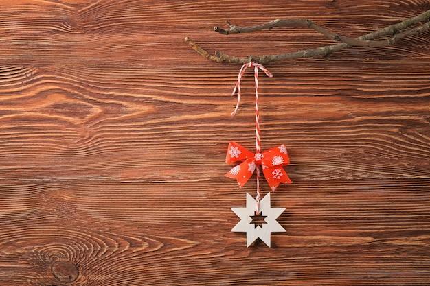 木製の背景に対して枝にぶら下がっているクリスマスの装飾