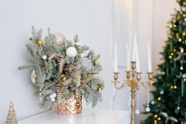 明るい色のクラシックなリビングルームまたはベッドルームのクリスマスの装飾。おもちゃとドレッサーの金の燭台が付いている金の花瓶のトウヒの枝