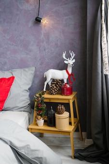 침실에 크리스마스 장식입니다. 빨간 스카프와 콘이 달린 흰 사슴
