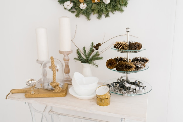 白いキッチンのクリスマス装飾:キャンドル、コーン、スプルース、プレート