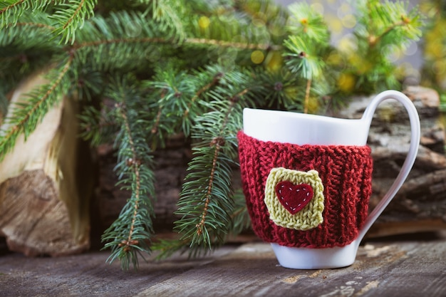 나무 테이블에 보케가 있는 크리스마스 장식 니트 모직 컵