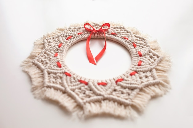 Christmas decor. macrame wreath for christmas and the new year on a white background. natural cotton thread, red tape. eco decor for home.
