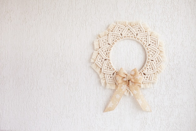 Christmas decor. macrame wreath for christmas and the new year on a white decorative plaster wall. natural cotton thread, linen tape. eco decor for home. copy space