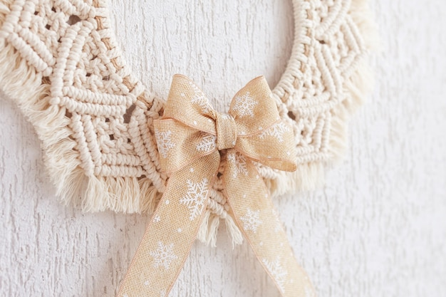 Christmas decor. macrame wreath for christmas and the new year on a white decorative plaster wall. natural cotton thread, linen tape. eco decor for home