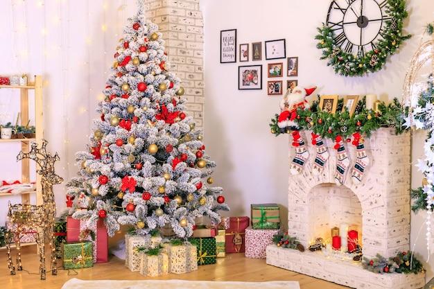 거실의 크리스마스 장식 방의 장식 크리스마스 snowcovered 전나무 나무 장난감 선물 상자 아래 나무 아늑한 벽난로
