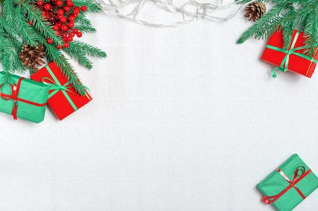 白い背景の上のクリスマスの装飾。クリスマスのモミの枝、赤いリボン、赤い装飾、輝き、白い背景の紙吹雪のギフトボックス。フラット横たわっていた、トップビュー