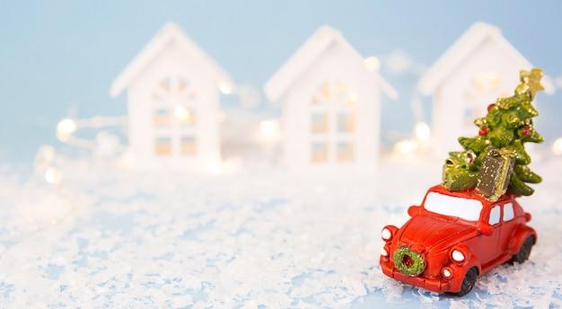 クリスマスの装飾-雪の上の赤いレトロな車は家の近くにクリスマスツリーを運ぶ