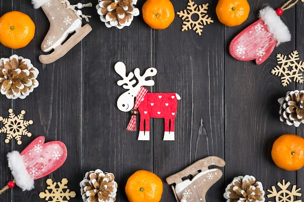 Christmas decor. skates, deer, mittens, snowflakes, tangerines, cones on wooden background flat lay