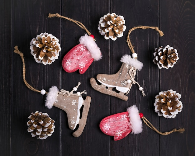 Christmas decor. skates, mittens, snowflakes, cones on wooden background flat lay