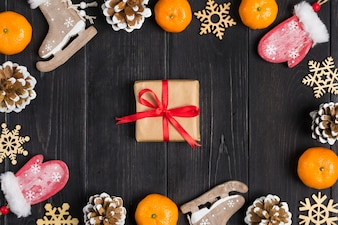Christmas decor. Skates, mittens, snowflakes, tangerines, cones, box on wooden background Flat lay