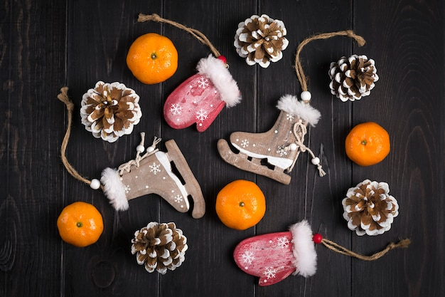 Christmas decor. skates, mittens, snowflakes, tangerines, cones on wooden background flat lay