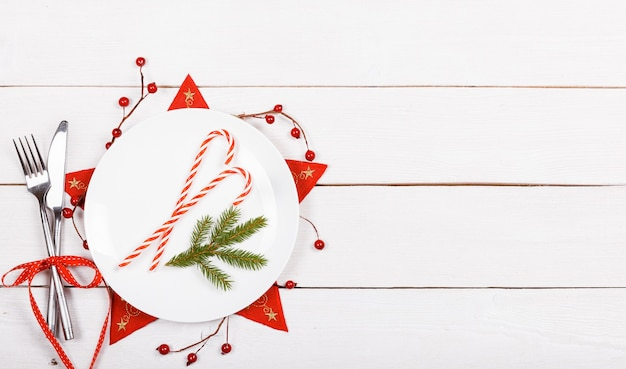 Christmas decor of the table white blank plate for your text flat lay top view