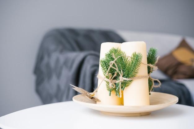 Рождественский декор белые свечи с искусственными еловыми ветками, перевязанными веревкой, стоят на тарелке