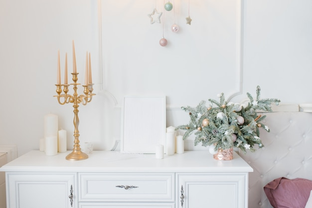 Christmas decor white chest of drawers in the bedroom or living room, candlestick, spruce arrangement and candles