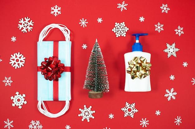 使い捨てのフェイスマスクと赤のハンドサニタイザーを備えたクリスマスの装飾。上面図