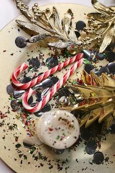 金のトレイにロリポップキャンドルと紙吹雪のクリスマスの装飾