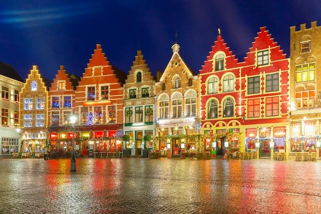 Украшенная и освещенная рождеством площадь old markt в центре брюгге, бельгия