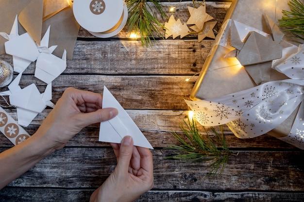 クリスマスに折り紙の紙の雄牛が飾られたギフトボックス。シンボル2021。ステップバイステップの説明。フラットレイ、上面図