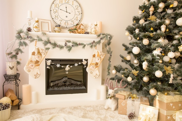 Christmas decorated house interior with fireplace, wall clock, xmas tree and presents under it. merry xmas and new year concept.