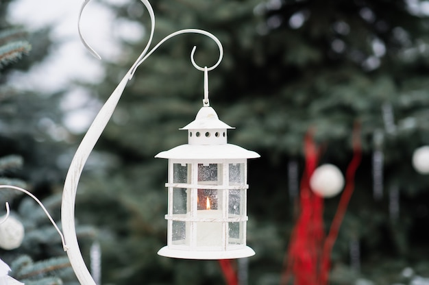 Christmas decorated lantern and candles on snow.